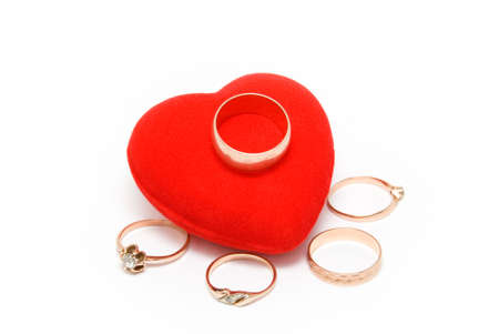 Five gold rings lay near to red velvet heart Stock Photo