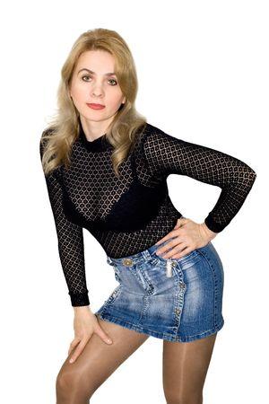 La belle femme dans une blouse noire et une jupe de jeans