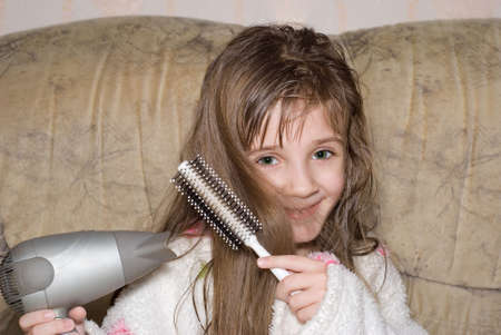 The little girl dries hair after bathing Stock Photo