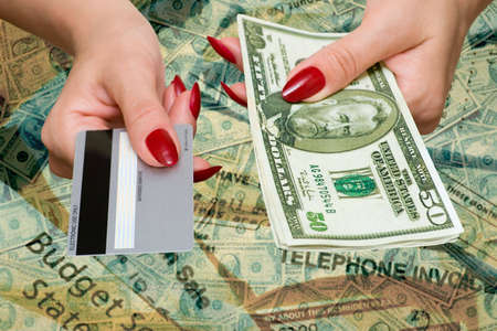 The female hand holds credit card and dollars Stock Photo