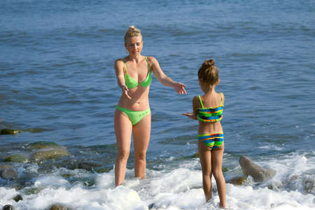 Mother and  daughter a standing in a sea  and extend each other hands  Фото со стока