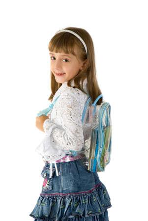 La petite fille dans une jupe de jeans avec un sac à dos