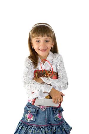 La petite fille à son fermoir sein une boîte avec un cadeau