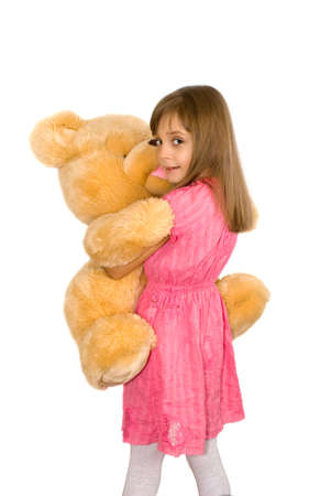 The little girl embraces the big toy bear