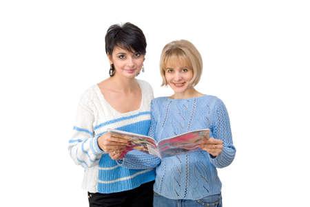 Two beautiful women look a magazine