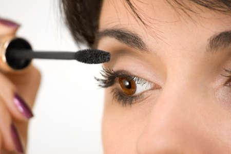 The beautiful girl is painting eyelashes Фото со стока