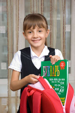The first-form girl  puts the ABC-book in a briefcase