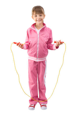 The little girl in a pink sports suit jumps through a jumping rope