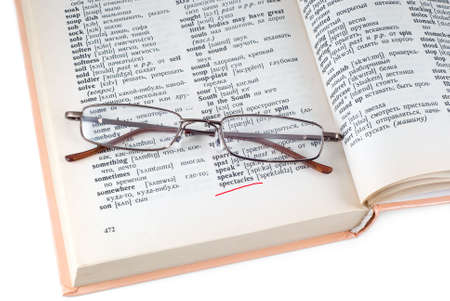 Spectacleses lay on the opened dictionary