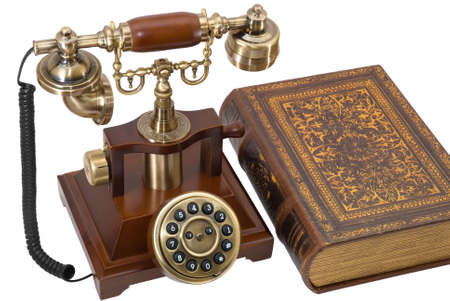 Ancient phone and book are photographed on the white background Stock Photo