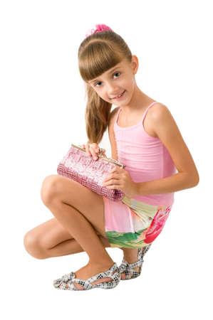 ni�o modelo: La chica con un bolso Rosa es fotografiada sobre el fondo blanco  Foto de archivo