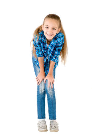 The girl in jeans and a checkered shirt is photographed on the white background