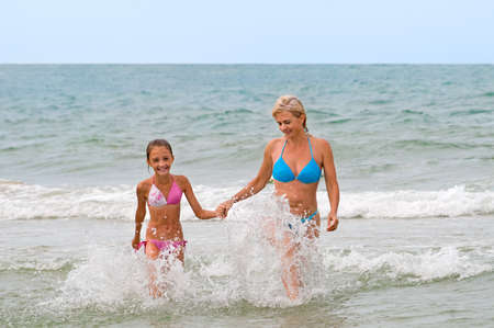 Mum with a daughter in foamy waves photo