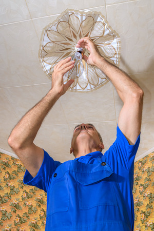 The electrician replaces a bulb in a chandelier