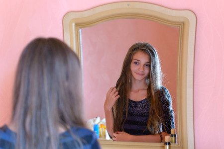 The girl looks in the mirror