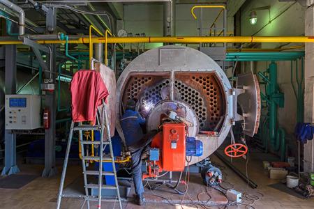 Trabajador reparación de la caldera con la ayuda de la soldadura Foto de archivo - 43792297