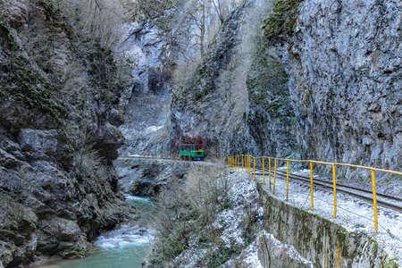 Tourist railway car rides along the mountain gorge Фото со стока