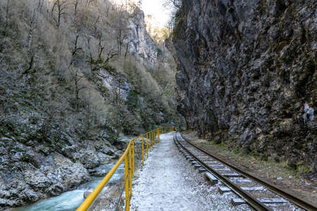 The railway in the mountain gorge goes along the river bank
