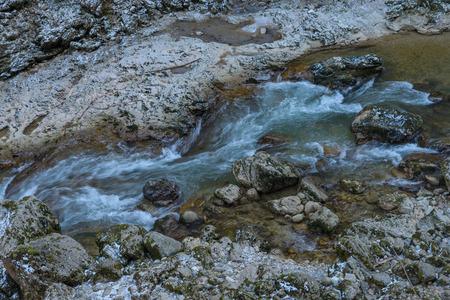 A stormy mountain river flows through the rocks Фото со стока