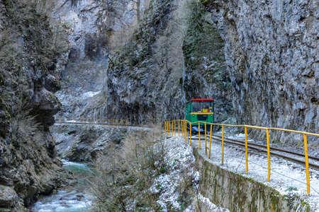 Tourist railway car rides along the mountain gorge Редакционное