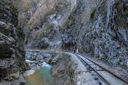 Tourists walk along a railway in a mountain gorge
