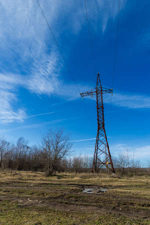 Power line support against blue sky background