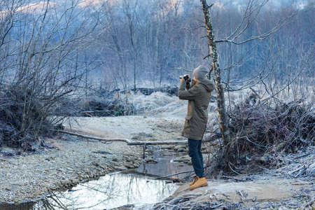 The photographer takes a picture of winter forest