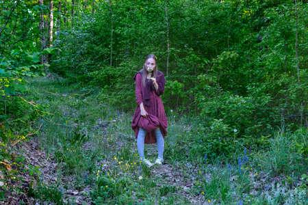 Girl on the edge of the forest sniffs honeysuckle flower