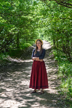 A girl in a red skirt is on a forest road Фото со стока