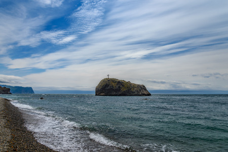 Rock with a cross stands in the sea against the cloudy sky