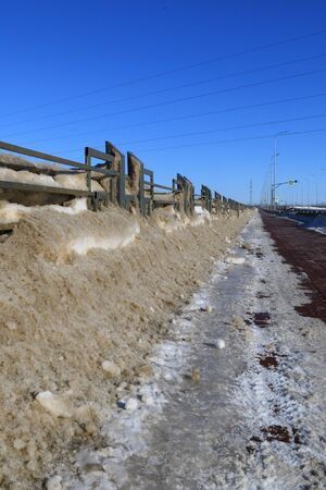 Dirty snow lies in drifts at the curb. Spring thaw and snow removal. Stock Photo