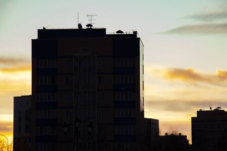 The darkening silhouettes of residential buildings are clearly visible against the sunset evening sky. City landscape.