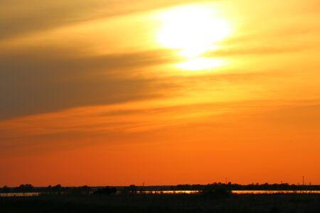 Beau ciel coucher de soleil sur des prairies qui s'assombrissent et une bande de rivière.