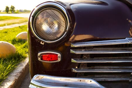 Headlight, chrome grille. An old car is parked at the curb. Retro and lush green grass
