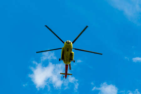 A yellow helicopter flies overhead. Against the blue sky, the rotors cut through the air Stock Photo