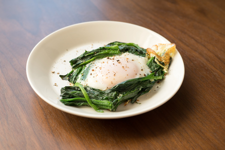 sunnyside: sunny-side up egg and sauteed spinach (breakfast) Stock Photo