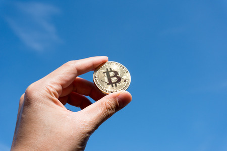 Bitcoin は、青い空を背景を保持 写真素材
