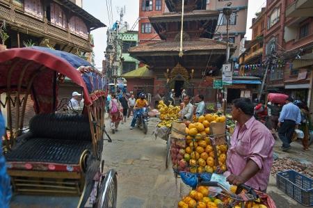 KATHMANDU, NEPAL - maggio 09,2013 - Mercato sulla strada a Kathmandu commercianti che vendono frutta fresca e ghirlande di fiori 9 maggio 2013 Kathmandu, Nepal