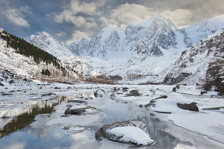 lake: Winter landscape. The remains are not of a frozen lake. Severe mountains peaks covered by snow. Russia, Siberia, Altai mountains, Chuya ridge.