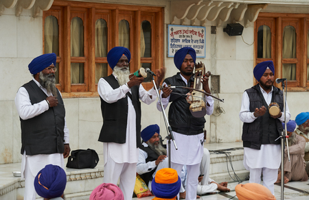 gurdwara: AMRITSAR, INDIA - February 18, 2015: Indian musicians playing local instruments at Golden Temple Harmandir Sahib also Darbar Sahib. Golden Temple is the holiest Sikh gurdwara located in city of Amritsar