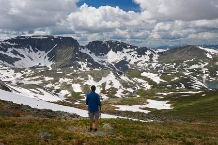 Hiker with backpack enjoying valley view from top of a mountain, Russia, Siberia, Altai mountains, Katun ridge.