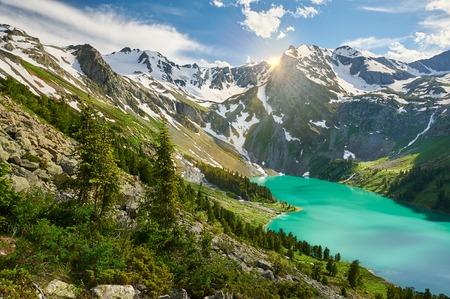 Sun among the mountain peaks. Beautiful summer landscape, mountain lake, Russia, Siberia, Altai mountains, Katun ridge. Stock Photo