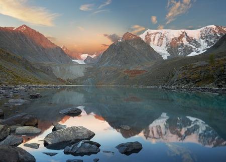 Sunrise among the mountain peaks. Beautiful summer landscape, mountain lake, Russia, Siberia, Altai mountains, Katun ridge.