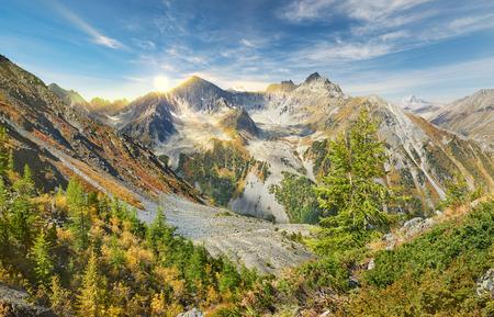 katun: Sun among the mountain peaks. Beautiful autumn landscape, view of the mountain range to the nearest Pass, Russia, Siberia, Altai Mountains, Katun Range. Stock Photo