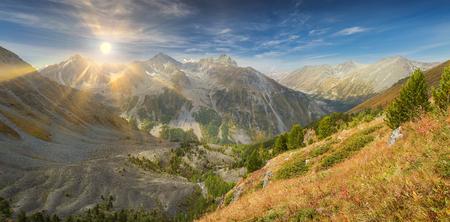 Sun among the mountain peaks. Beautiful autumn landscape, view of the mountain range to the nearest Pass, Russia, Siberia, Altai Mountains, Katun Range. Stock Photo