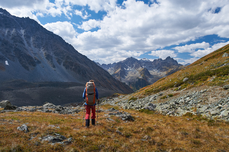 Young sportive hiker trekking in the mountains. Sport and active life concept. View of the mountain range to the nearest Pass, Russia, Siberia, Altai Mountains.