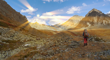 A bright sunny day, young sportive man hiker trekking in the mountains. Sport and active life concept. View of the mountain range to the nearest Pass, Russia, Siberia, Altai Mountains. Stock Photo