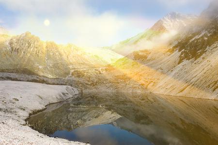 katun: Mountain snow capped peaks in a misty haze. Sun among the mountain peaks. Beautiful autumn landscape, mountain lake, Russia, Siberia, Altai Mountains, Katun Range.