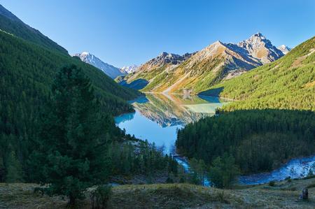 The cloudless early morning sun illuminates the mountain peaks painted in autumn.. Beautiful autumn landscape, view of the mountain range, Russia, Siberia, Altai Mountains, Katun Range.
