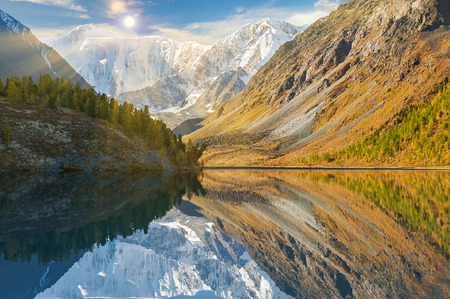 gold capped: Landscape of Roerich. Sunny day Akkem Valley. In the background is Belukha Mountain. A beautiful autumn landscape, a view of the mountain lake, Russia, Siberia, Altai, Katunsky ridge. Stock Photo